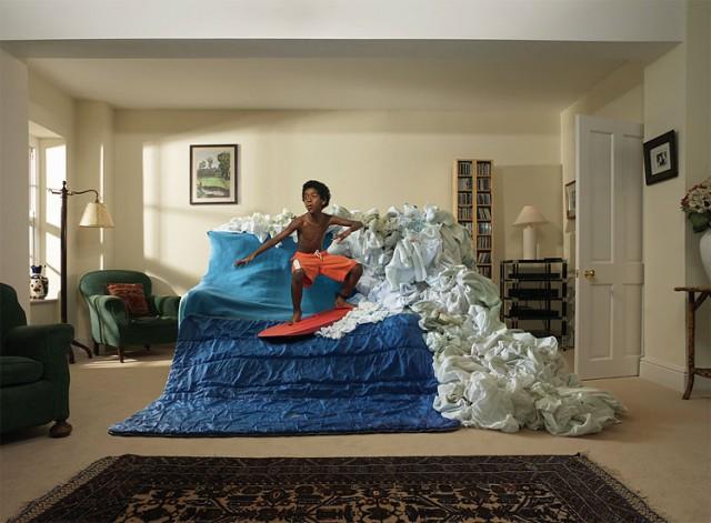 ソファーや布団を波にしてサーフィンする少年の写真