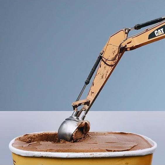 アイスクリームをすくうショベルカーの写真